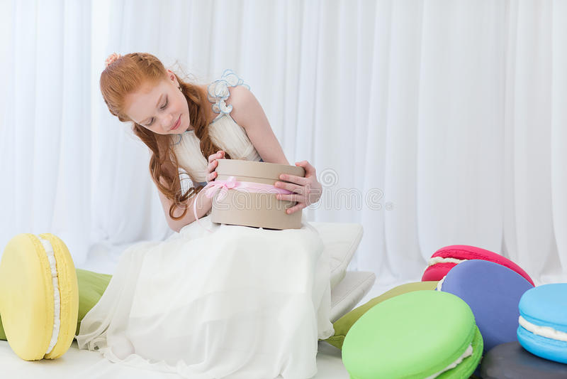 Muchacha que juega con la caja de regalo imagen de archivo