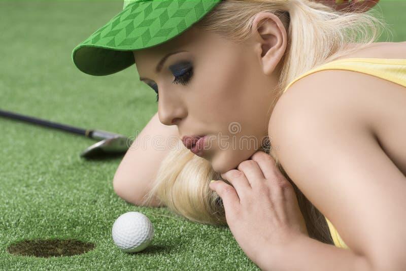 Muchacha que juega con la pelota de golf y la mano debajo imágenes de archivo libres de regalías