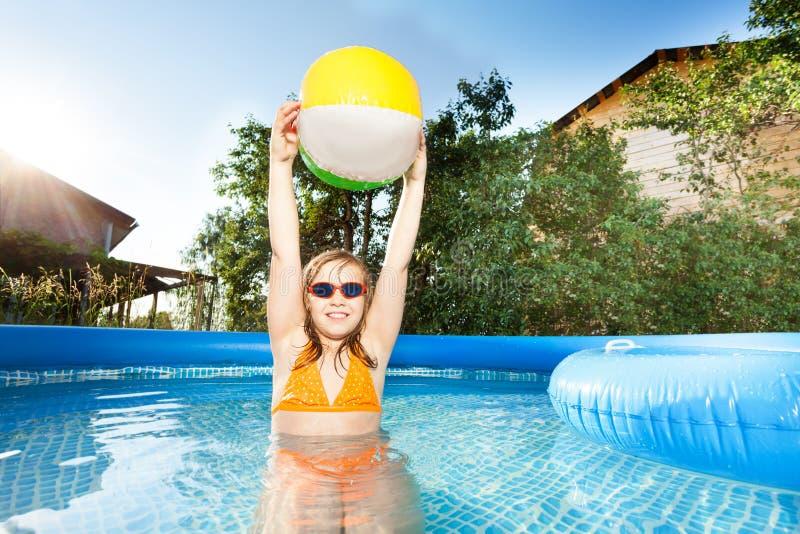 Muchacha que juega con la pelota de playa en la piscina fotos de archivo libres de regalías