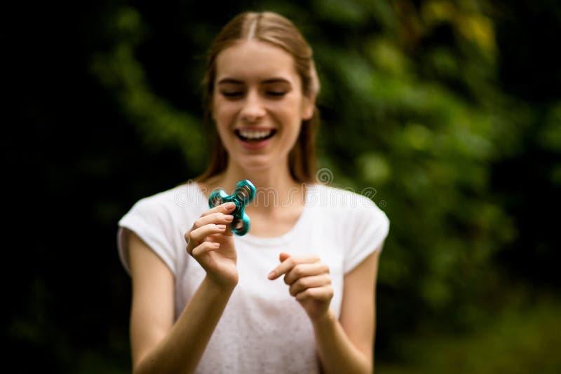 Muchacha que juega con la sonrisa del hilandero de la persona agitada imágenes de archivo libres de regalías
