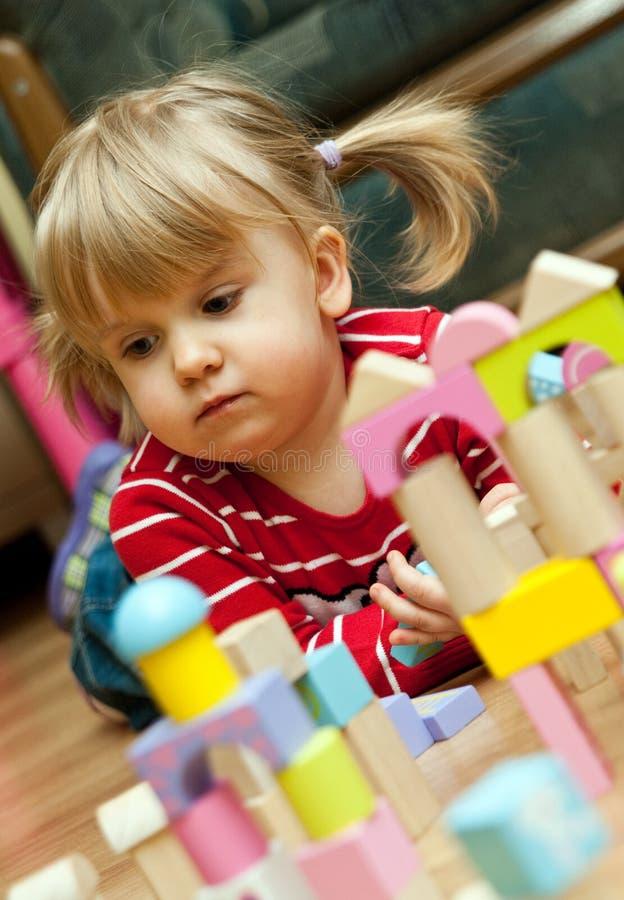 Muchacha que juega con los bloques de madera imagenes de archivo