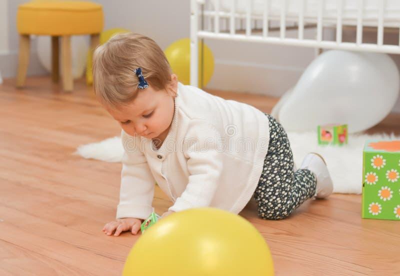 Muchacha que juega con los juguetes en el cuarto blanco del ` s de los niños foto de archivo libre de regalías