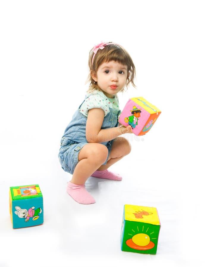Muchacha que juega con los juguetes en el suelo fotografía de archivo libre de regalías