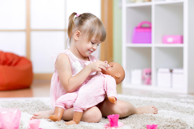 Muchacha que juega con su muñeca foto de archivo libre de regalías