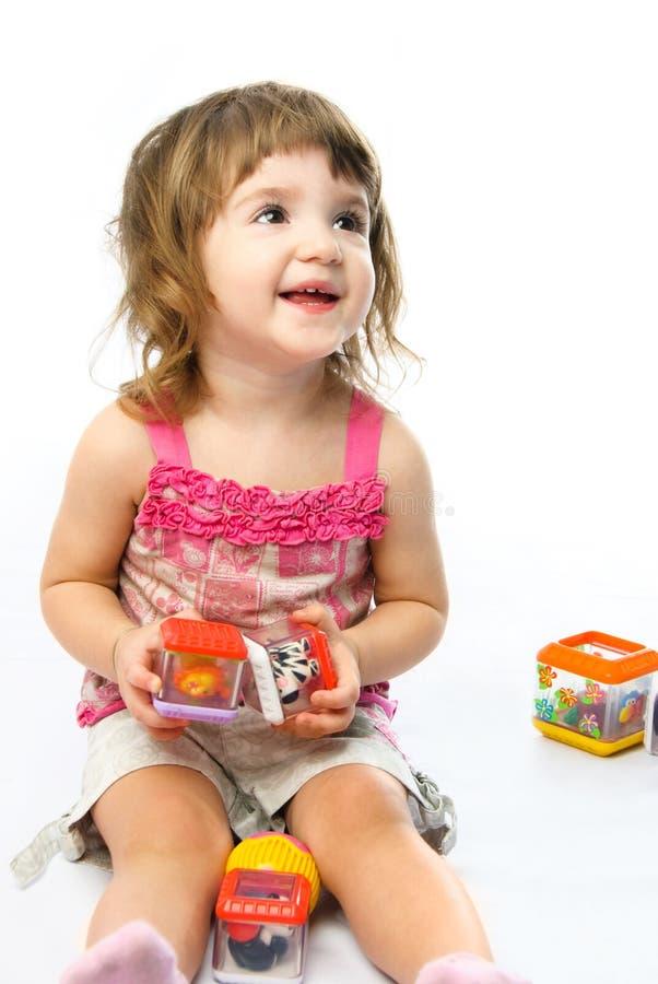 Muchacha que juega con sus juguetes imagen de archivo
