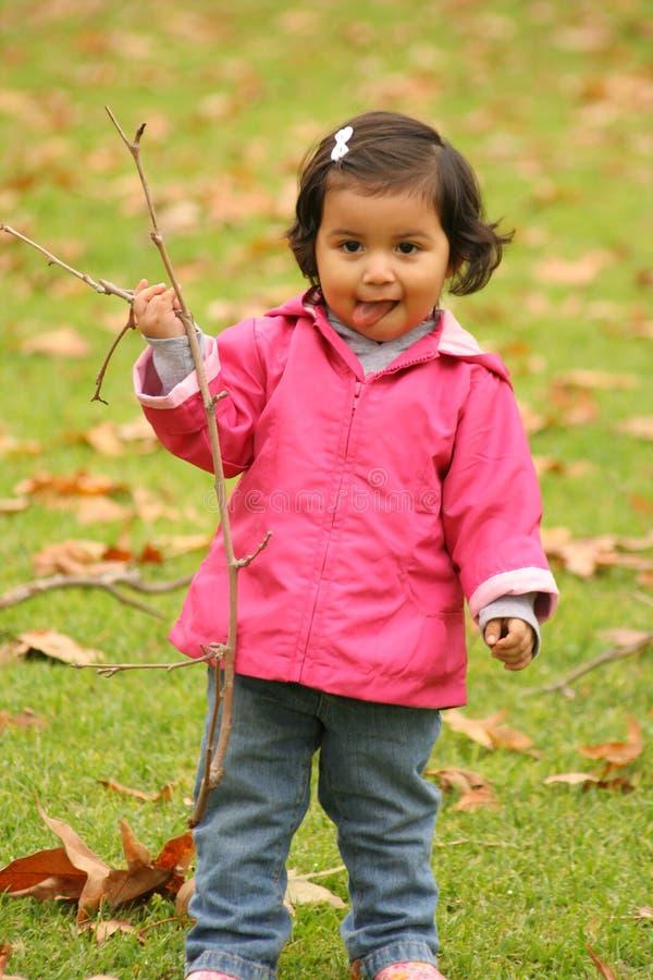 Muchacha que juega con un palillo. foto de archivo libre de regalías