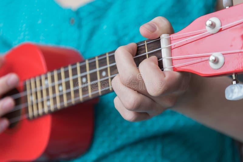 Muchacha que juega el acorde en el ukelele rojo del soprano fotografía de archivo