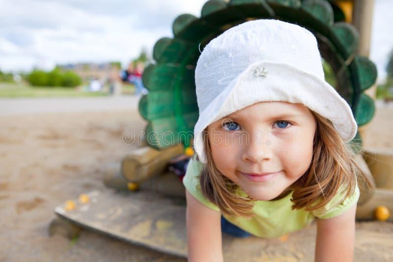 Muchacha que juega en el patio de los niños imagen de archivo