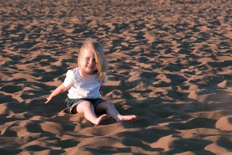 Muchacha que juega en la arena que se sienta en la playa imágenes de archivo libres de regalías