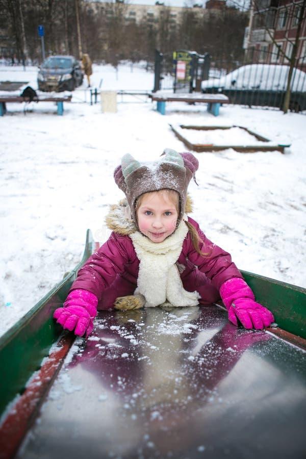 Muchacha que juega en la calle nevosa fotografía de archivo