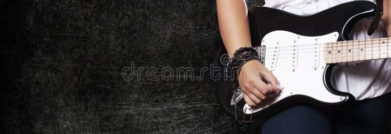 Muchacha que juega en la guitarra en fondo oscuro del grunge foto de archivo libre de regalías