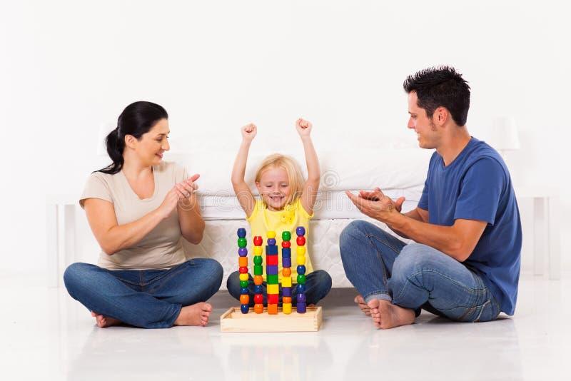 Muchacha que juega los juguetes con los padres imagen de archivo