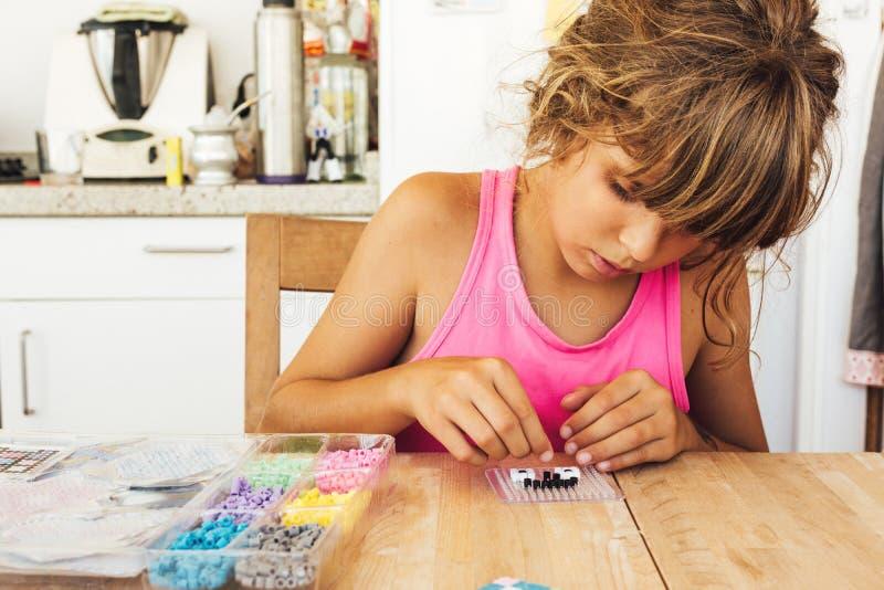 Muchacha que juega a un juego de mesa en la tabla de cocina imágenes de archivo libres de regalías