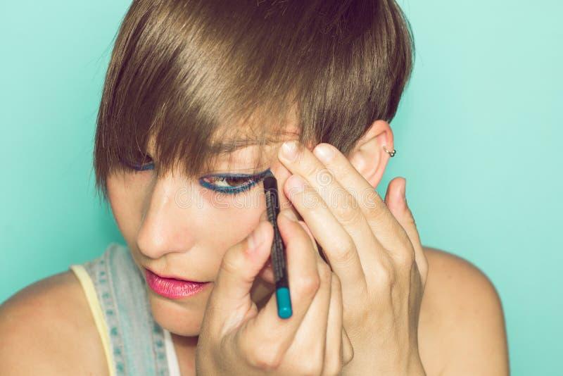 Muchacha que la pinta ojos Mujer en maquillaje imagen de archivo libre de regalías