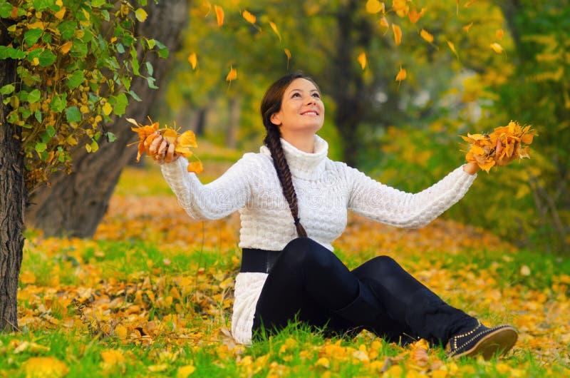 Muchacha que lanza las hojas de otoño secas en el aire imágenes de archivo libres de regalías