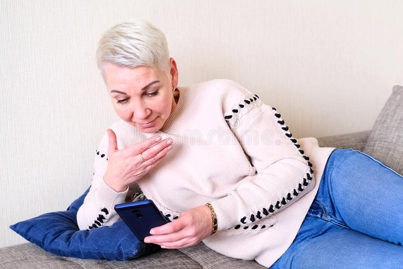 Muchacha que lee SMS en el smartphone La emoción de la sorpresa alegre El corte de pelo corto de las mujeres Perfil elegante de m imagen de archivo