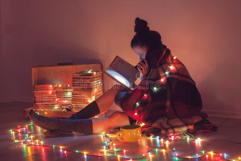 Muchacha que lee un libro debajo de la manta en casa imagenes de archivo