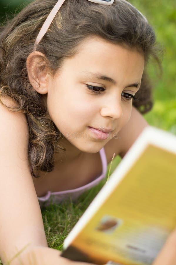 Muchacha que lee un libro en el jardín fotos de archivo libres de regalías