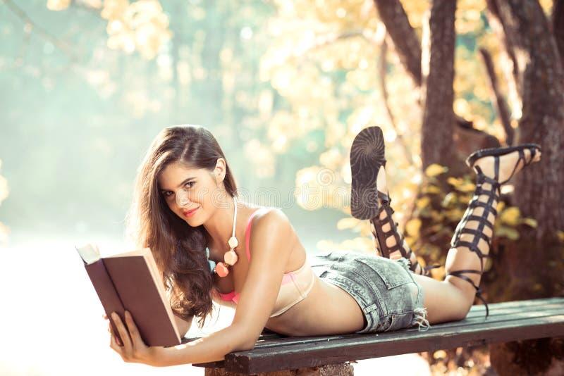 Muchacha que lee un libro en parque imagen de archivo