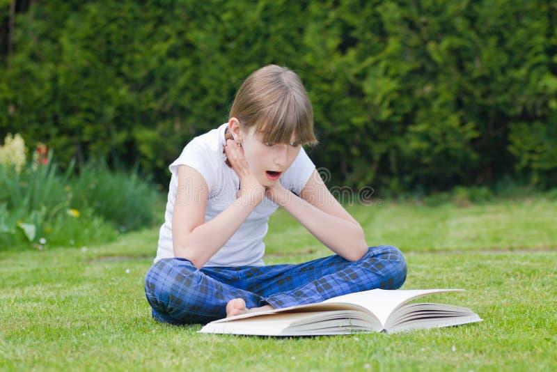 Muchacha que lee un libro en un jardín fotografía de archivo libre de regalías
