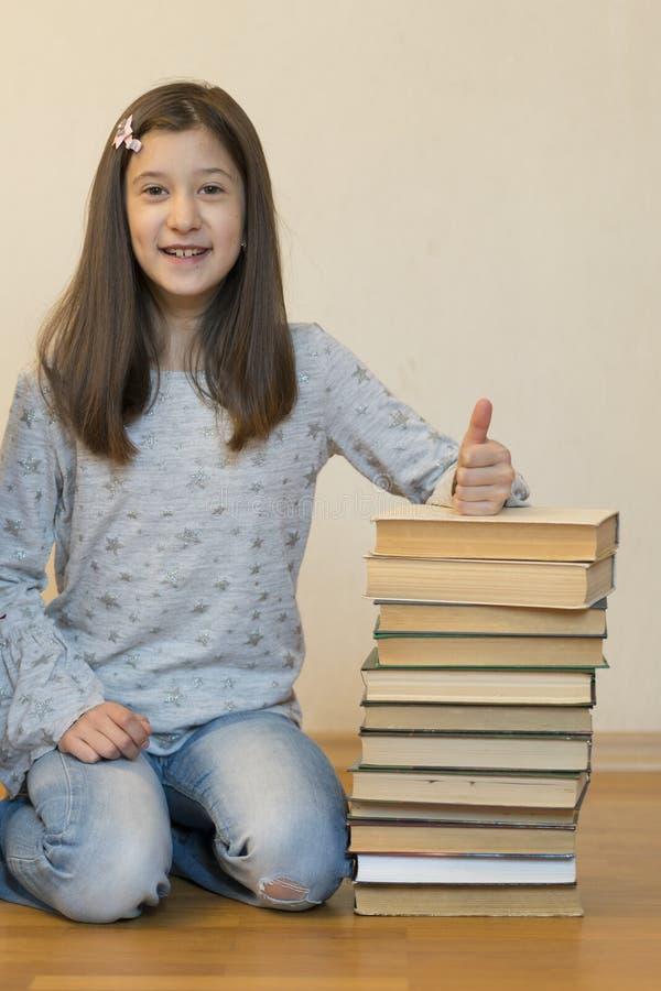 Muchacha que lee un libro que se sienta en el piso en un apartamento Libro de lectura lindo de la muchacha en casa educaci?n y co foto de archivo