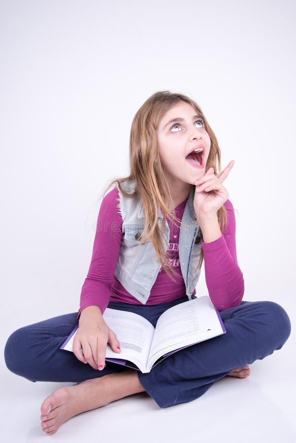 Muchacha que lee un libro y que tiene una idea imágenes de archivo libres de regalías