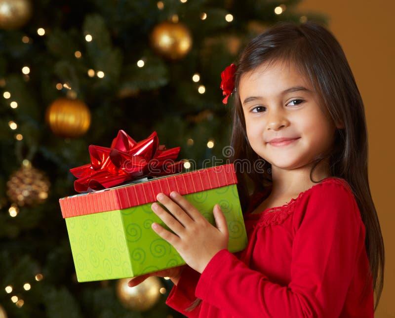 Muchacha que lleva a cabo el regalo de Navidad delante del árbol foto de archivo libre de regalías