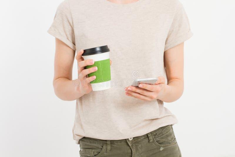 Muchacha que lleva a cabo el teléfono y el coffe blancos Teléfono móvil aislado en la trayectoria de recortes blanca dentro Visió imagen de archivo