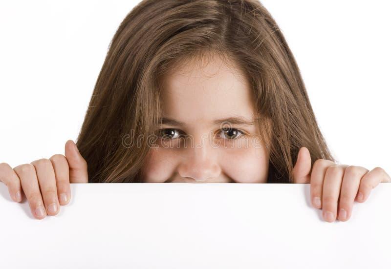 Muchacha que lleva a cabo la tarjeta de mensaje en blanco imagen de archivo libre de regalías