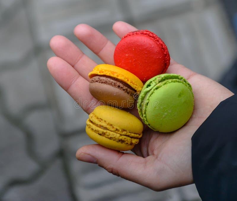 Muchacha que lleva a cabo las manos francesas coloridas de los macarons imagenes de archivo