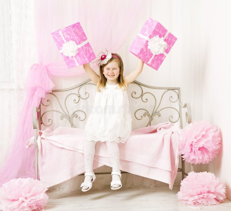 Muchacha que lleva a cabo presentes de cumpleaños Niño feliz con imagen de archivo
