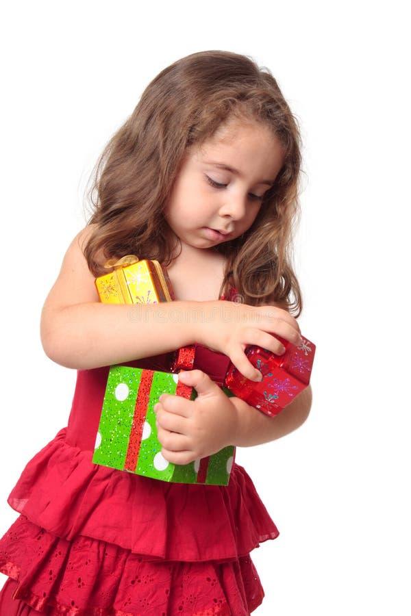 Muchacha que lleva a cabo un brazado de regalos de Navidad imagen de archivo libre de regalías