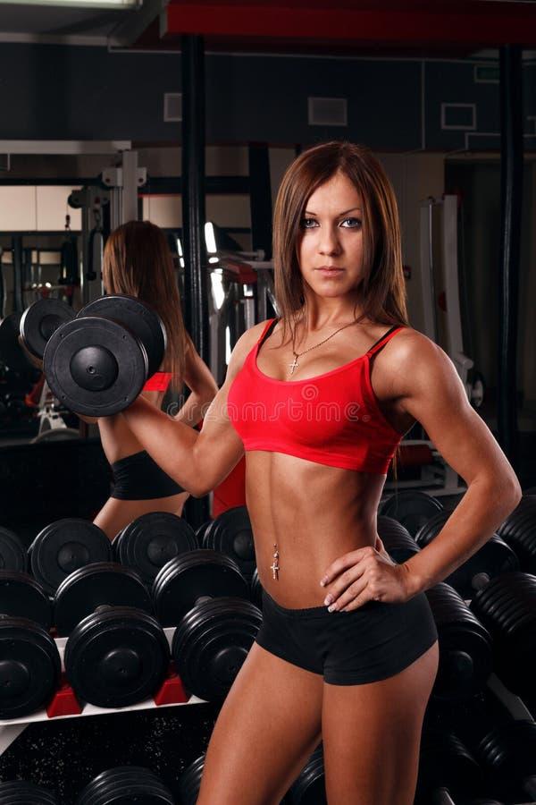 Muchacha que lleva a cabo una pesa de gimnasia fotografía de archivo