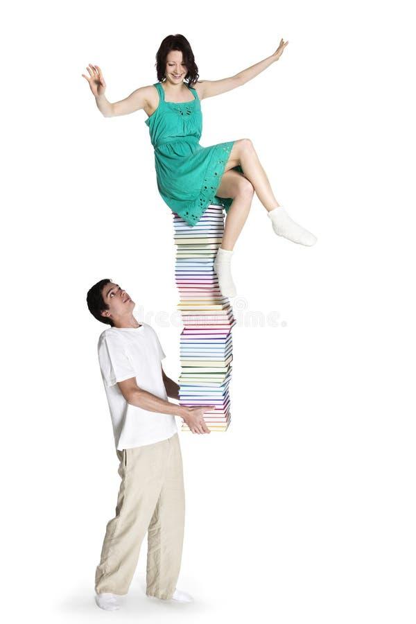 Muchacha que lleva del muchacho en pila de libro. foto de archivo libre de regalías
