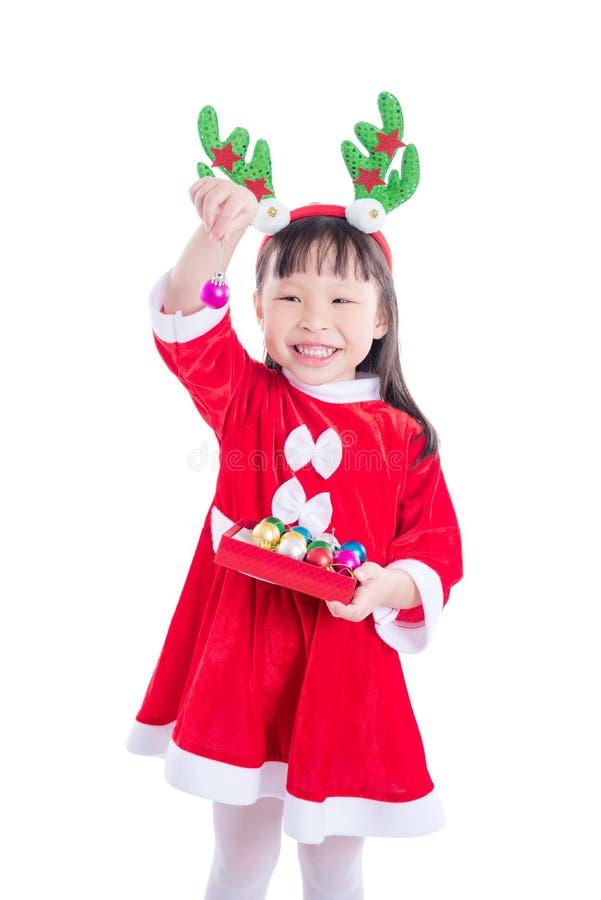 Muchacha que lleva el vestido de Papá Noel que sostiene la bola para la decoración imagen de archivo libre de regalías