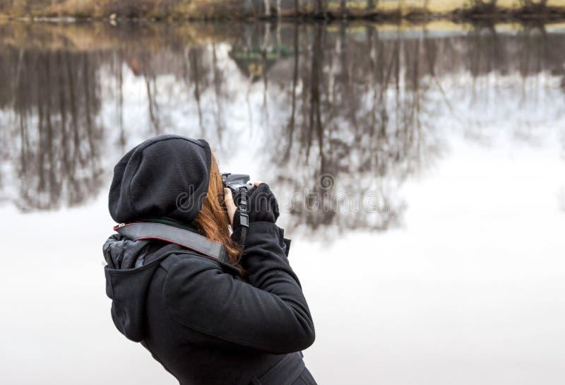 muchacha que lleva imágenes en cámara durante un viaje el lago fotos de archivo