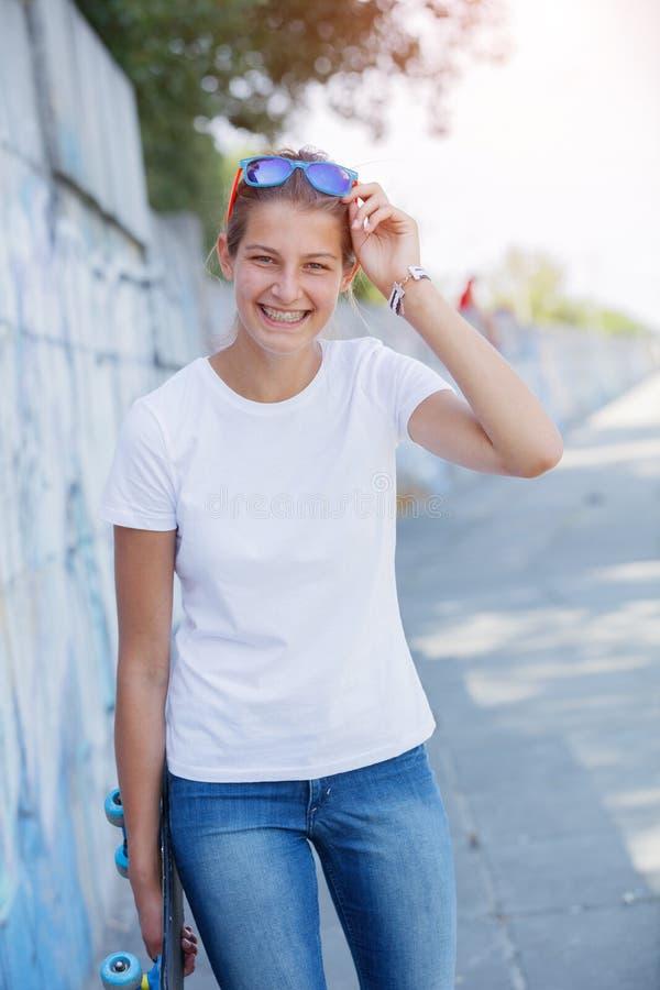 Muchacha que lleva la camiseta blanca en blanco, vaqueros que presentan contra la pared áspera de la calle foto de archivo