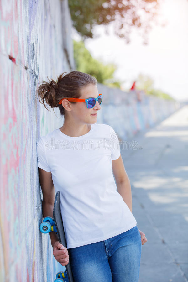 Muchacha que lleva la camiseta blanca en blanco, vaqueros que presentan contra la pared áspera de la calle fotos de archivo