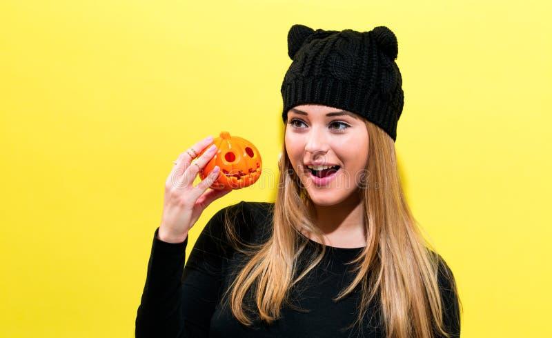 Muchacha que lleva sosteniendo una calabaza de Halloween fotografía de archivo libre de regalías