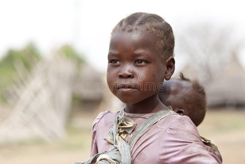 Muchacha que lleva a su hermana en Sudán del sur fotos de archivo