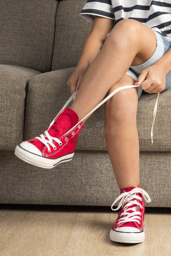 Muchacha que lleva un par de zapatillas de deporte rojas imagenes de archivo