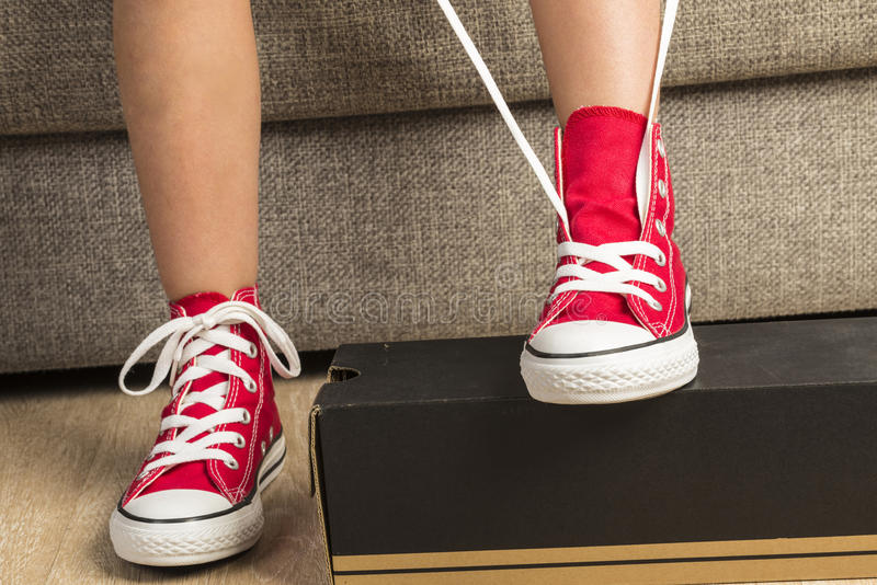 Muchacha que lleva un par de zapatillas de deporte rojas imagen de archivo libre de regalías