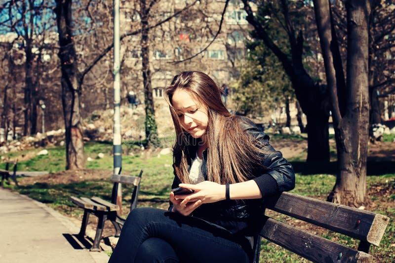Muchacha que manda un SMS en el teléfono elegante fotografía de archivo