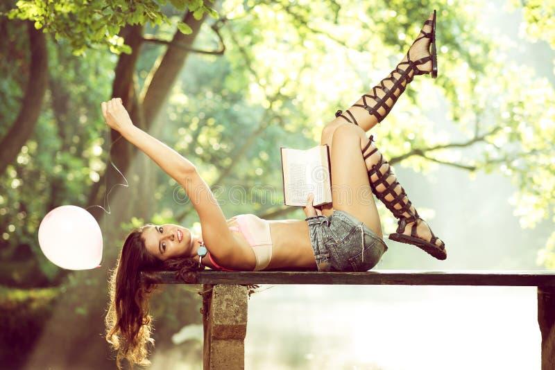 Muchacha que miente en banco con el libro y el globo fotos de archivo libres de regalías