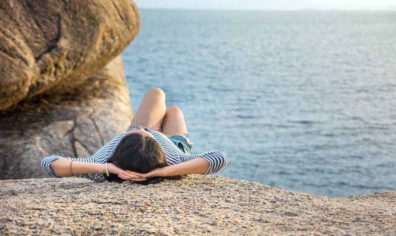 Muchacha que miente en el acantilado sobre la playa en la puesta del sol foto de archivo
