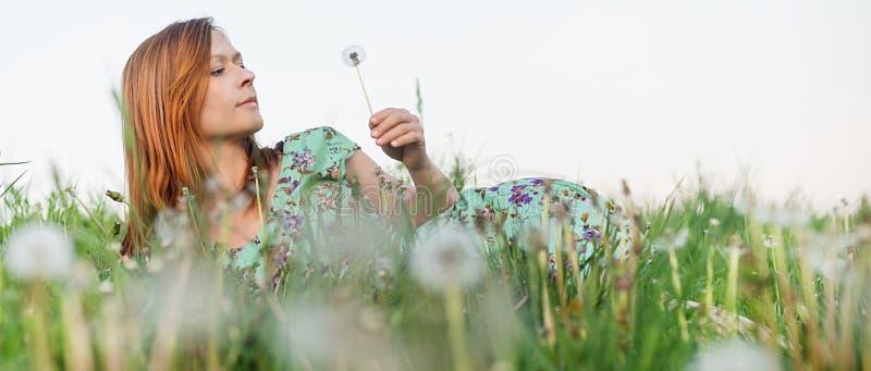 Muchacha que miente en el campo de flor fotos de archivo