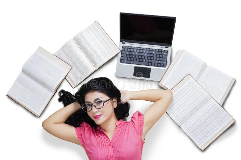 Muchacha que miente en el piso con los libros y el ordenador portátil fotografía de archivo