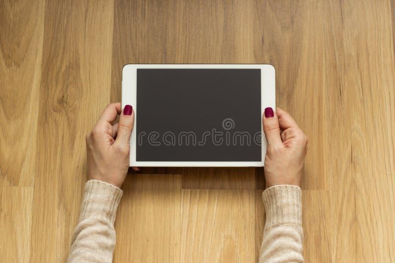 Muchacha que miente en el piso que sostiene una tableta foto de archivo libre de regalías