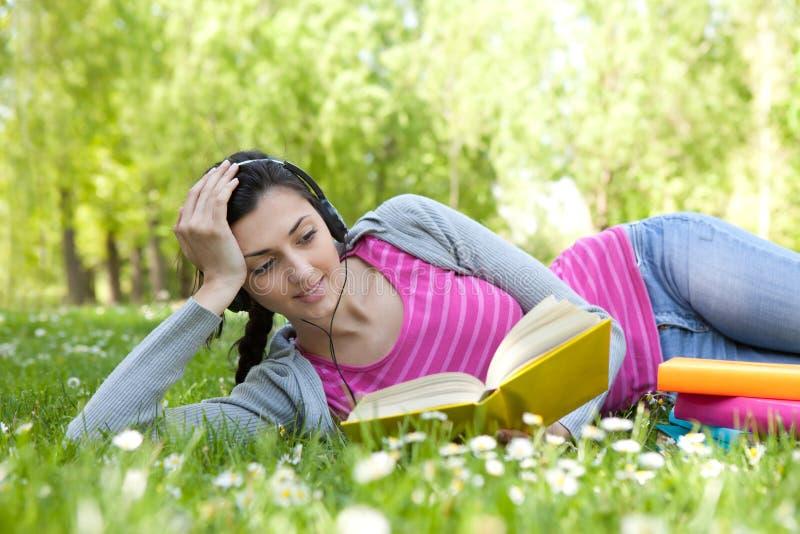 Muchacha que miente en hierba en parque con el libro y el receptor de cabeza foto de archivo libre de regalías
