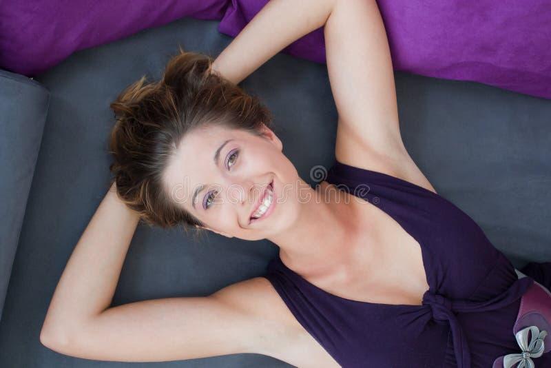 Muchacha que miente en la cama con sonrisa grande imagenes de archivo